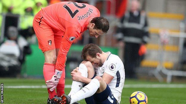 Asmir Begovic checks on harry Kane after their collision