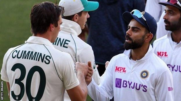 India's Virat Kohli (facing camera) fist bumps Australia's Pat Cummins (back to camera) on the third day of the first cricket Test match between Australia and India in Adelaide