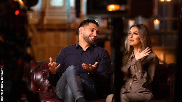 Amir Khan and Faryal Makhdoom being filmed on a sofa.
