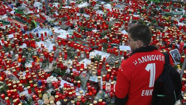 HANOVER, GERMANY - NOVEMBER 15: A fan of the Hannover 96 football club looks at a sea of candles for goalie Robert Enke shortly before a memorial service prior to Enke�s funeral at AWD Arena on November 15, 2009 in Hanover, Germany. Tens of thousands of fans paid their last tribute to Enke, who was also goalie for the German national team, following Enke�s suicide on November 10. (Photo by Sean Gallup/Getty Images)