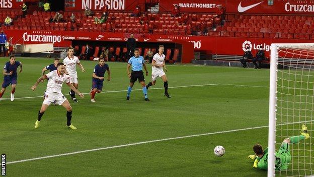 Atletico Madrid keeper Jan Oblak saves Lucas Ocampos' first-half penalty against Sevilla
