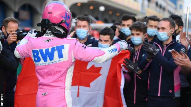 Lance Stroll holds up a Canadian flag