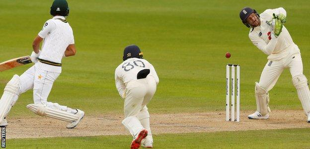 Jos Buttler misses the stumping of Shan Masood