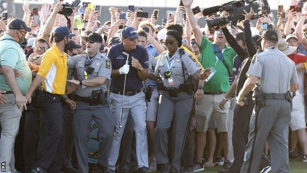 Phil Mickelson emerges through the crowd on to the 18th green