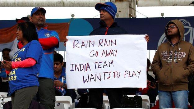 An India fan holds a sign saying 'Rain rain go away India team wants to play'