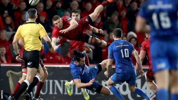Leinster's James Lowe takes out Munster's Andrew Conway in the air