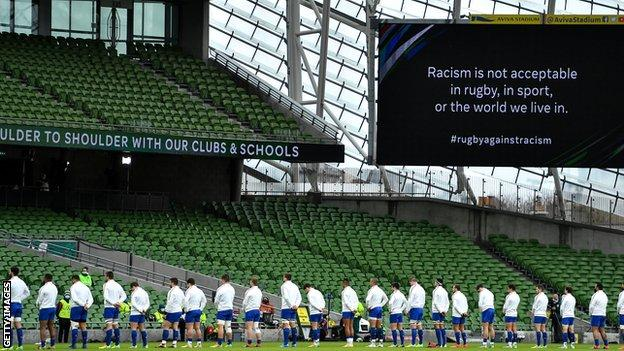 "Rugby players stood in a line with the words ""Racism is not acceptable in rugby, in sport, or the world we live in"" on the big screen"