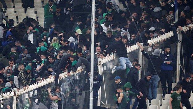 Fans climb a fence