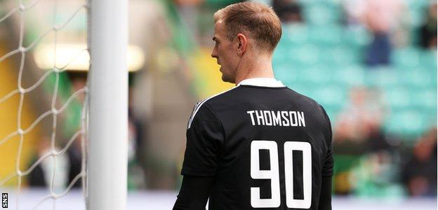 Joe Hart wearing a top that says 'Thomson 90' during Celtic's warm-up against Ross County