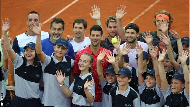 Novak Djokovic with players and ballboys and girls