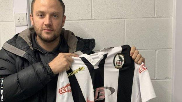 Kyle Perry holds up a Coalville Town shirt after signing for the non-league club