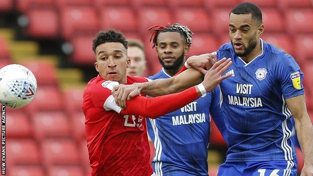 Curtis Nelson of Cardiff and Jacob Brown of Barnsley challenge for the ball