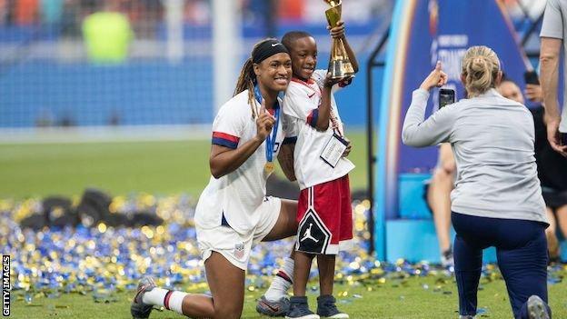 Jessica McDonald, oğlu Jeremiah ile birlikte Kadınlar Dünya Kupası kupasını elinde tutuyor.