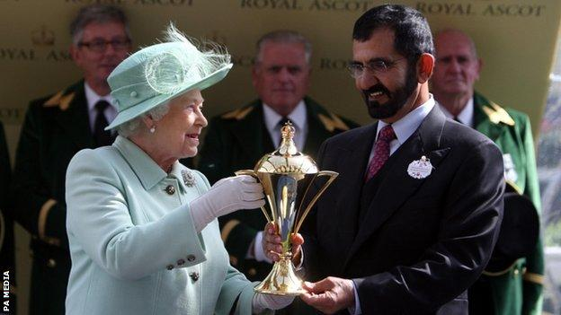 Queen Elizabeth II presents the Gold Cup to Sheikh Mohammed Al Maktoum following Colour Vision's win at Royal Ascot in 2012