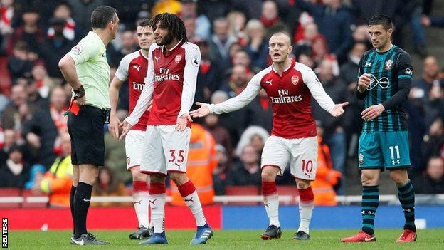 Referee Andre Marriner puts his red card in his pocket after sending off Mohamed Elneny, who complains