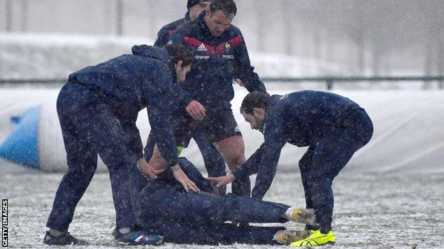 French team-mates check on Lionel Beauxis as he lies on the ground at training on Friday