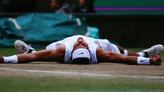 Rafael Nadal lies on his back with his arms spread out as he celebrates his first Wimbledon triumph