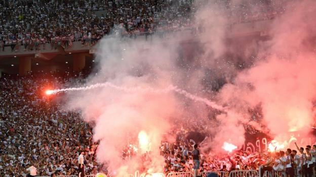 Zamalek fans light flares (They can't treat us like animals,' says football player 'duped' out of $1m)