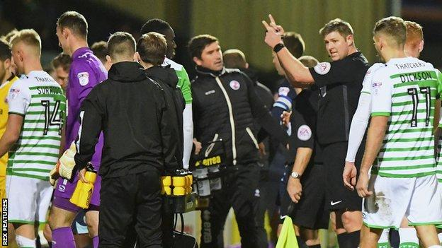 Referee Brett Huxtable orders Yeovil and Crawley players off the pitch as a drone flies over head at Huish Park