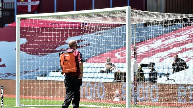 Ground staff sprays goal posts at Villa Park