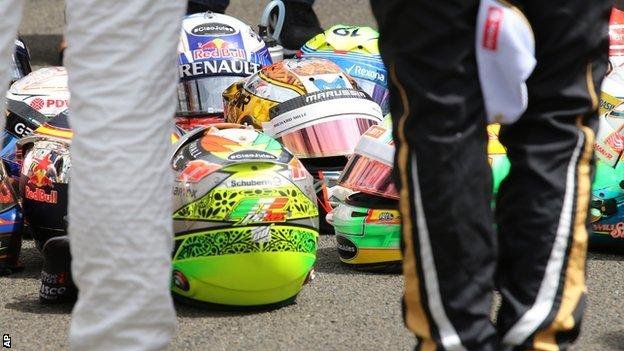 The drivers placed their helmets on the ground before gathering around for the minute's silence. Jules Bianchi's helmet was among them