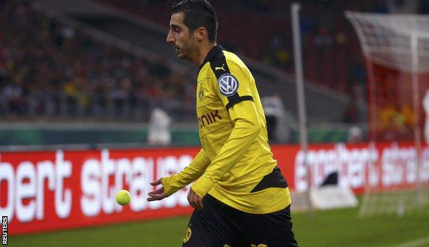 Henrikh Mkhitaryan throws one of the balls off the pitch