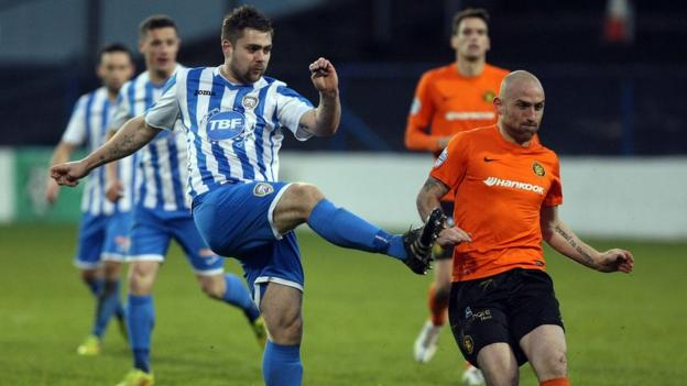 In-form Coleraine striker James McLaughlin clears the ball in his side's 2-1 win over Carrick as Barry Johnston looks on