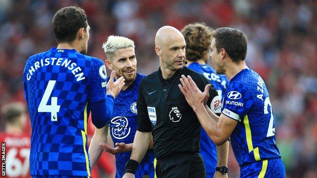 Chelsea players surround referee Anthony Taylor