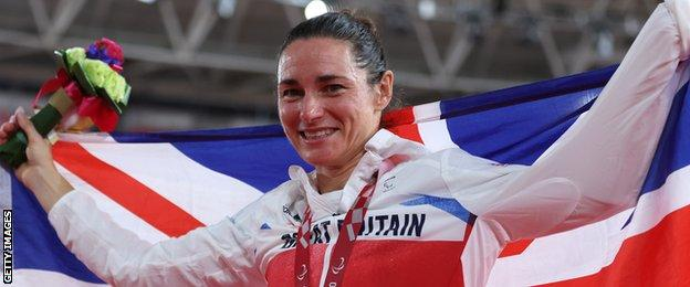 Sarah Storey holds aloft a Union flag to celebrate her individual pursuit gold medal at the Tokyo Paralympics