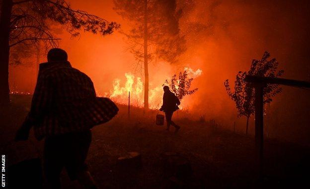 Οι χωρικοί κουβαλούν κουβάδες γεμάτους νερό για να σβήσουν μια φωτιά που πλησίαζε στα σπίτια τους στο Αμούντο στο Μακάο, κεντρική Πορτογαλία, 21 Ιουλίου 2019.