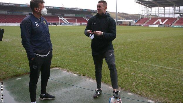 Referee Thomas Bramall explains his decision to Oxford United assistant coach Craig Short