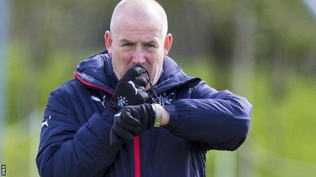 Mark Warburton blows a whistle as he takes Rangers training