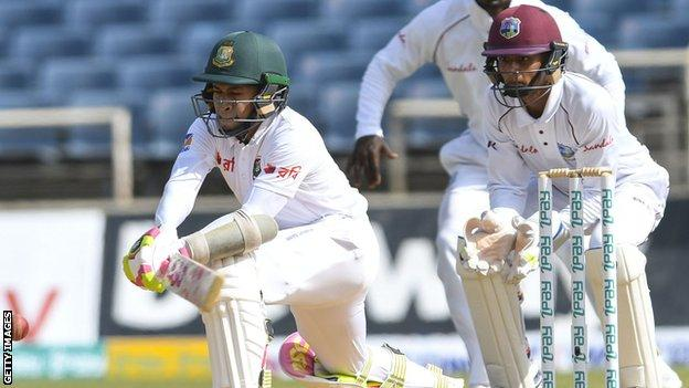 Bangladesh's Mushfiqur Rahim reverse-sweeps, watched by West Indies keeper Shane Dowrich