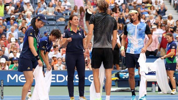 The court being cleaned after Lloyd Harris spilt his drink