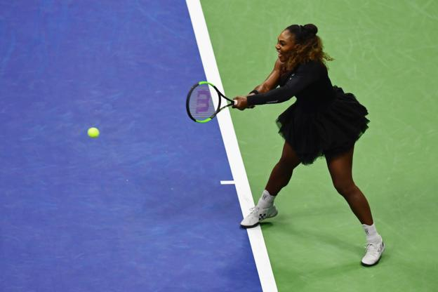 Serena Williams returns the ball during her women's singles first-round match against Magda Linette