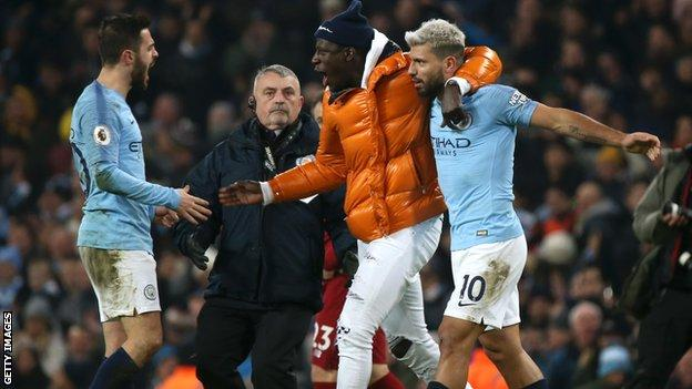 Benjamin Mendy runs on to the pitch to hug Sergio Aguero, with a steward watching on.
