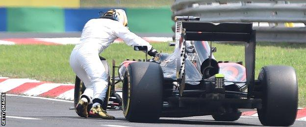 McLaren's Fernando Alonso pushes his car after it broke down in qualifying at the Hungarian Grand Prix