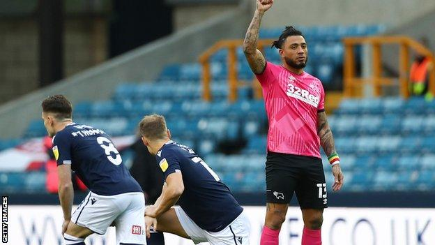 Derby County's Colin Kazim-Richards raises his fist as Millwall players take a knee before kick-off