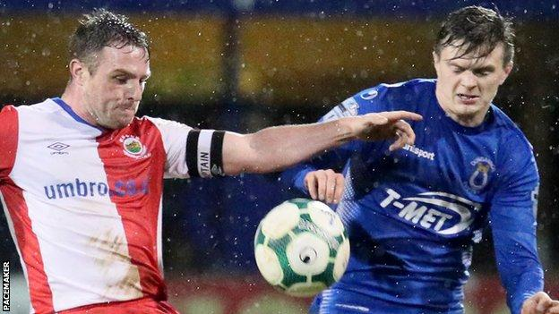 Linfield skipper Jamie Mulgrew in action against Paul McElroy of Dungannon Swifts