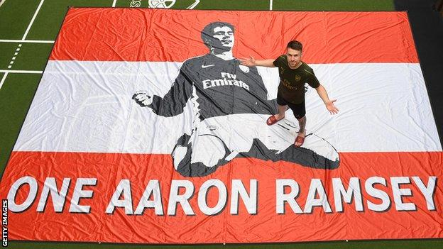 Aaron Ramsey poses on a flag which says 'One Aaron Ramsey'. The flag was made by Arsenal fans