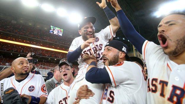 Houston Astros players hoist second baseman Jose Altuve on their shoulders