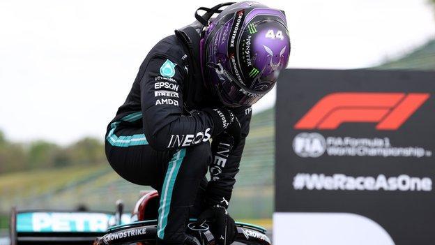 Lewis Hamilton kneels down on top of his Mercedes