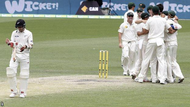 New Zealand tailender Trent Boult walks off the field as Australian players celebrate victory