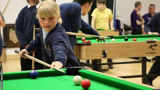 A young girl playing snooker.