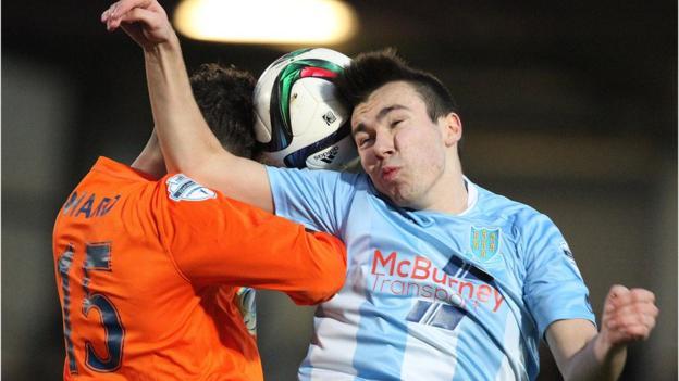 Linfield goalscorer Sean Ward and Ballymena substitute Matthew Ferguson jump for a high ball at the Showgrounds