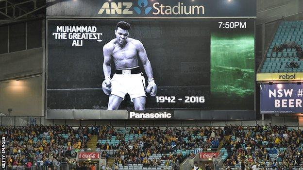 Spectators sit beneath a tribute to boxing legend Muhammad Ali before the international friendly football match between Australia and Greece in Sydney