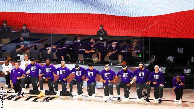Les joueurs des Lakers s'agenouillent pendant l'hymne national tout en portant des t-shirts arborant un `` vote ''