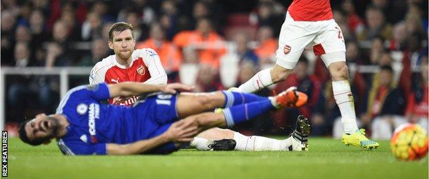 Per Mertesacker looks on after fouling Diego Costa