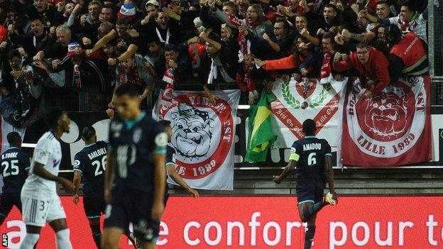 Lille supporters celebrate before the barrier collapses