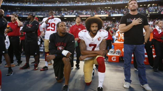 Boyer, (far right) stands with his hand on his heart as the anthem plays. Kaerpernick kneels with team-mate Eric Reid (left)